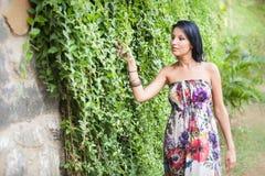 Beautiful brunette girl  walking near creeper wall Royalty Free Stock Image