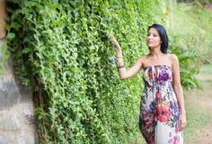 Beautiful brunette girl  walking near creeper wall Royalty Free Stock Images
