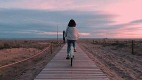 Beautiful brunette girl walks ahead of sea beach at dawn stock footage