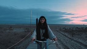 Beautiful brunette girl walks ahead of sea beach at dawn stock video
