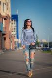 Beautiful brunette girl walks through the city Stock Image