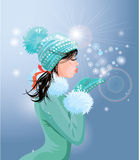 Beautiful brunette girl with warm blue winter hat is blowing Royalty Free Stock Photos