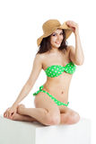 Beautiful brunette girl wearing green swimsuit sitting Stock Photos