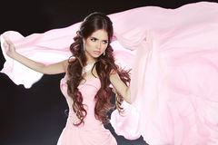Beautiful brunette girl wearing in pink dress isolated on black Royalty Free Stock Images