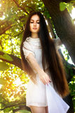 Beautiful brunette girl in white dress with long hair Royalty Free Stock Images
