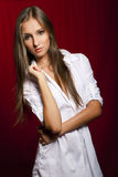 Beautiful brunette girl in white before red. Background Royalty Free Stock Image