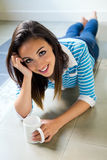 Beautiful brunette girl who is lying on the floor and drinking c Royalty Free Stock Photography