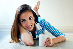 Beautiful brunette girl who is lying on the floor and drinking c Royalty Free Stock Image