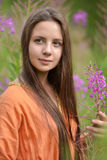 Beautiful brunette girl and willow-herb Stock Image