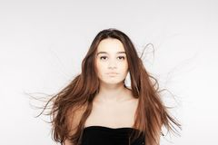 Beautiful brunette girl with windy hair. Brunette girl with windy hair looking at camera Royalty Free Stock Images