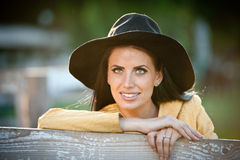 Free Beautiful Brunette Girl With Country Look Near An Old Wooden Fence. Attractive Woman With Black Hat And Yellow Coat Stock Photos - 58036443