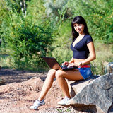 Beautiful brunette girl working with laptop sitting on a stone Royalty Free Stock Photo