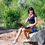 Beautiful brunette girl working with laptop sitting on a stone Stock Images