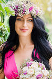 Beautiful brunette girl in a wreath of flowers, holding in his h. And bouquet. Portrait of bride Royalty Free Stock Image