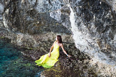 Beautiful brunette girl in yellow dress sits on a rock near mountain lake Stock Photography