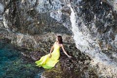 Beautiful brunette girl in yellow dress sits on a rock near mountain lake.  Stock Photography