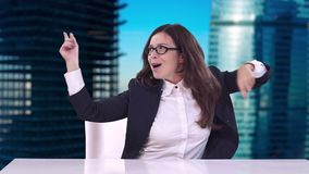 Beautiful brunette with glasses sitting in a business suit at office Desk and enjoys a successful career