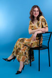 Beautiful brunette with glasses and a yellow dress on a blue Royalty Free Stock Photos