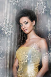 Beautiful brunette in a golden retro dress Royalty Free Stock Photography