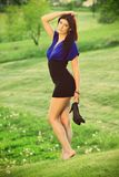 Beautiful brunette on a golf course. Beautiful brunette in a black and blue dress posing on a golf course, in a nature,  fashion photography Stock Images