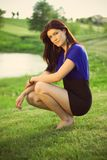 Beautiful brunette on a golf course. Beautiful brunette in a black and blue dress posing on a golf course, in a nature, she kneels on a grass, fashion Royalty Free Stock Photography