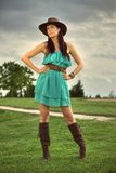 Beautiful brunette on a golf course. Beautiful brunette in a green dress, cowboy hat and high boots posing on a golf course, in a nature,  fashion photography Stock Photos