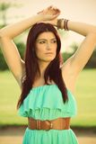Beautiful brunette on a golf course. Beautiful brunette in a green dress posing on a golf course, in a nature,  fashion photography Stock Photo