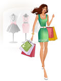 Beautiful brunette in a green dress standing near the shop Stock Images