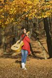 Beautiful brunette guitar player girl in the forest Royalty Free Stock Photography