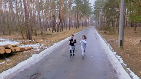 Beautiful brunette with handsome guy makes jogging in the morning in the forest. Young sport people makes morning exercises outdoors. Pretty woman and handsome stock footage