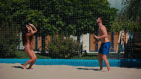 Beautiful brunette and handsome guy playing volleyball on the beach. Young couple playing volleyball on the beach. The people standing in front of each other stock footage