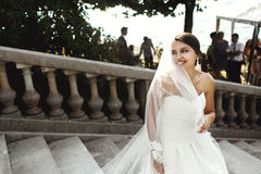 Beautiful brunette happy bride in white dress posing on stone st Royalty Free Stock Photography