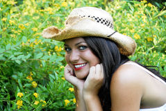 Beautiful Brunette with Hat. Beautiful brunette posing for a portrait wearing a straw hat next to a garden with yellow flowers. She's smiling with beautiful red Stock Image