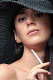 Beautiful brunette in hat smokes Royalty Free Stock Photos