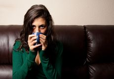Beautiful brunette having tea or coffee on a couch. Beautiful brunette drinking tea or coffe while sitting on a leather couch Royalty Free Stock Photography