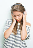Beautiful brunette in headphones, eyes closed. Beautiful young brunette listening to music with headphones, eyes closed Royalty Free Stock Photography