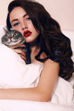 Beautiful brunette holding a cat ,lying on bed in bedroom royalty free stock images