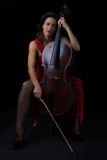 Beautiful brunette holding cello in red dress Stock Photo