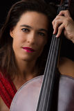 Beautiful brunette holding cello with selective light in red dre Royalty Free Stock Photos