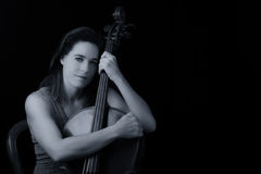 Beautiful brunette holding cello with selective light in red dre Royalty Free Stock Photography