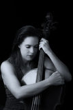Beautiful brunette holding cello with selective light in red dre Royalty Free Stock Image