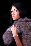 Beautiful brunette holding her coat. Portrait of a beautiful woman with luxurious coat Stock Images