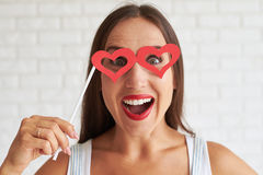Beautiful brunette holding red glasses-mask in the shape of hear. Smiling woman holding red glasses-mask in the shape of heart, white brick wall on background Royalty Free Stock Photo