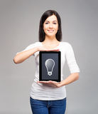 Beautiful brunette holding a tablet with an idea Royalty Free Stock Photos