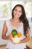 Beautiful brunette holding vegetables bowl Stock Photo