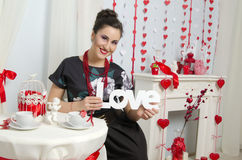 Beautiful brunette holding the word love. Beautiful brunette in a black dress holding the word love Stock Image