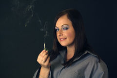 Beautiful Brunette Holds a Smoldering Match Royalty Free Stock Photo