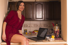 Beautiful brunette at home, in red nightdress Royalty Free Stock Photos