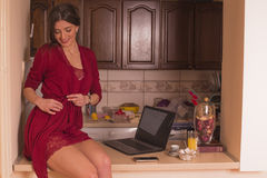Beautiful brunette at home, in red nightdress Royalty Free Stock Image