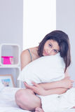 Beautiful brunette hugging her pillow Royalty Free Stock Photos